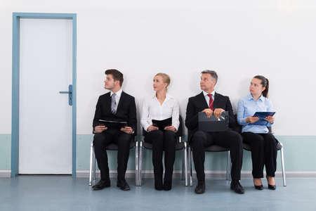 file d attente: Groupe de gens d'affaires avec des fichiers assis sur une chaise Pour Donner Entretien
