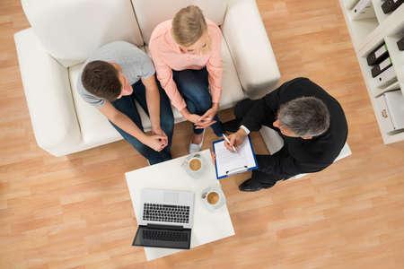 portapapeles: Vista de ángulo alto de Consultor maduro muestra el documento a Joven pareja en casa