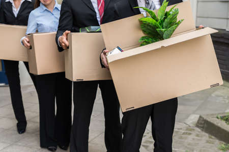 unemployment: Close-up Of Unemployed Businesspeople Carrying Cardboard Boxes Stock Photo