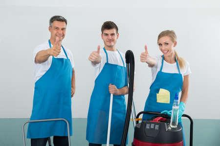 personal de limpieza: Grupo de Porteros Felices Con Limpieza Equipos Mostrando el pulgar en signo
