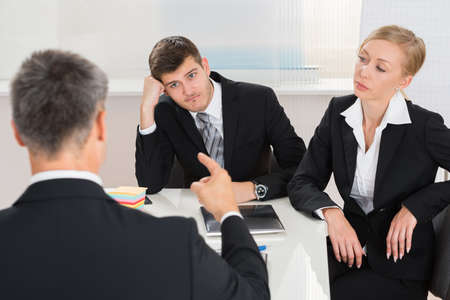jefe enojado: Grupo de tres empresarios que tienen argumento en el lugar de trabajo