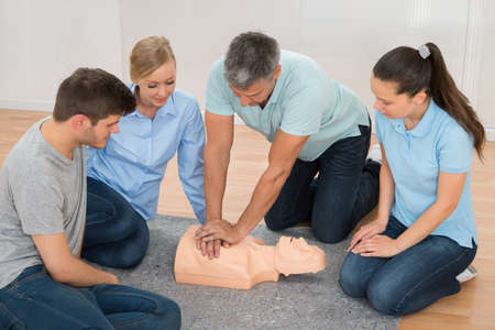 reanimate: Mature Male Instructor Showing Cpr Training On Dummy To His Student