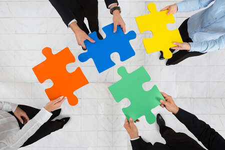 jigsaw puzzle pieces: High Angle View Of Businesspeople Team Holding Colorful Puzzle Pieces In Hands