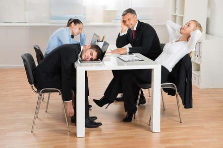 ビジネスマンのオフィスで机に座っている間に飽きて