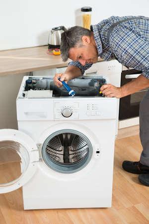 Full length of handyman checking washing machine with flashlight in kitchen Reklamní fotografie