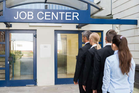 queue: Group Of Businesspeople Standing In Row Outside The Job Center