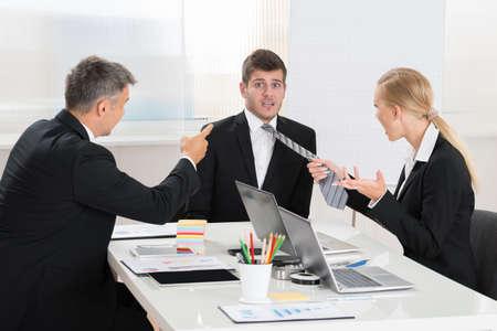 jefe enojado: Dos Empresarios peleando Para Joven Empresario En El Escritorio De Oficina