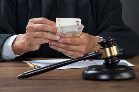 corrupt: Male corrupt judge counting money at table in courtroom