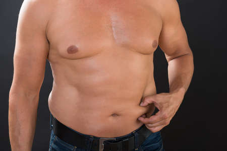 Midsection of shirtless man measuring stomach fat against gray background