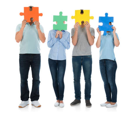 jigsaw piece: Group Of People Covering Face With Puzzle Pieces Over White Background