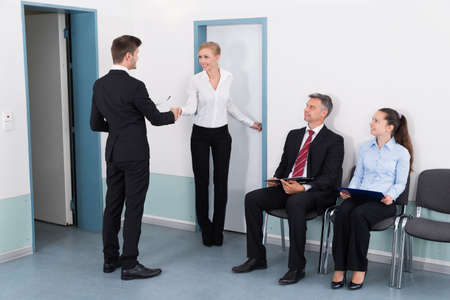 job: Businesswoman Shaking Hands With Man In Front Of People Waiting For Job Interview In Office