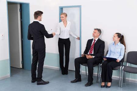 entrevista de trabajo: Empresaria que sacude las manos con el hombre en frente de personas esperando la entrevista de trabajo en la oficina