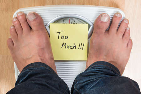low scale: Low section of man standing on weight scale with too much sign