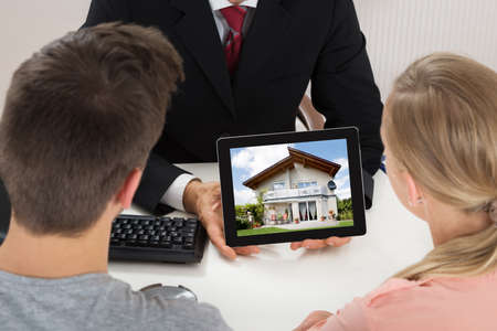 showing: Close-up Of Agent Showing House On Digital Tablet To Couple At Desk