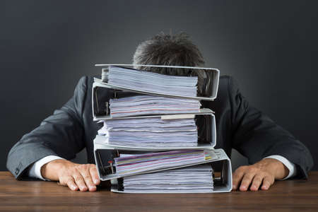 Frustrated businessman with lot of files on desk against gray background Stockfoto