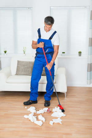 brooming: Full length of male janitor sweeping crumpled papers on floor in living room
