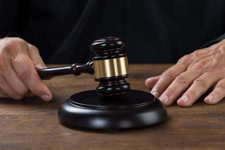 striking: Cropped image of male judge striking the gavel at table Stock Photo