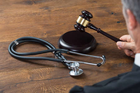 justice: Cropped image of judge hitting gavel with stethoscope in courtroom Stock Photo