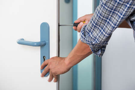 Cropped image of technician fixing lock in door with screwdriver at home