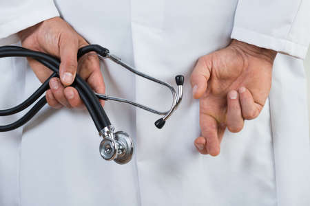 finger crossed: Midsection rear view of male doctor with fingers crossed Stock Photo