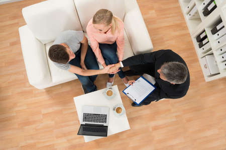 High Angle View Of Man Shaking Hands With Estate Agent At Home Stok Fotoğraf