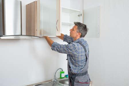 Vue arrière de la fixation serviceman armoire avec un tournevis dans la cuisine Banque d'images - 47216900