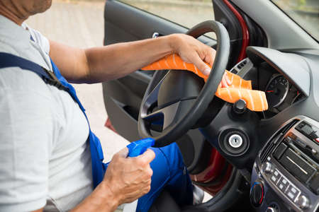 vehicle interior: Side view of mature worker cleaning steering wheel of car Stock Photo