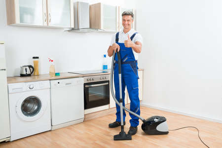 up service: Full length portrait of male janitor cleaning floor with vacuum cleaner in kitchen