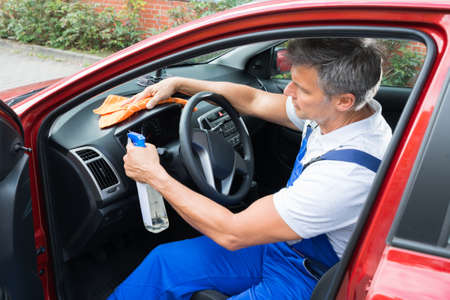 Mature man cleaning car interior Stock Photo