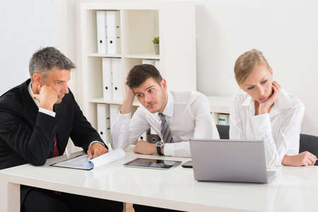 disinterested: Group Of Businesspeople Getting Bored Sitting At Desk In Office