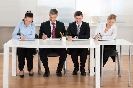 Happy Businesspeople Writing On Clipboard At Desk Stock Photo