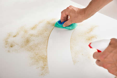 cropped image: Cropped image of male janitor cleaning counter with detergent spray bottle and sponge Stock Photo