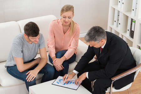 Mature Financial Advisor Showing Graph On Paper To Young Couple Foto de archivo