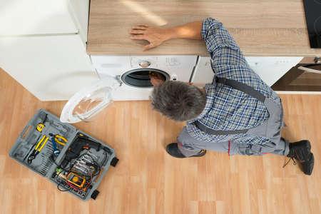 high angle: High angle view of handyman checking washing machine at home Stock Photo