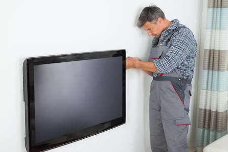 high definition television: Side view of mature technician installing television at home Stock Photo