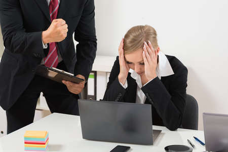 harassment: Boss With Clipboard Blaming To The Female Employee For Bad Results Stock Photo