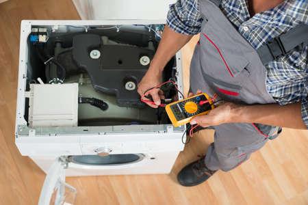 High angle de vue du technicien contrôle machine à laver avec multimètre numérique dans la cuisine