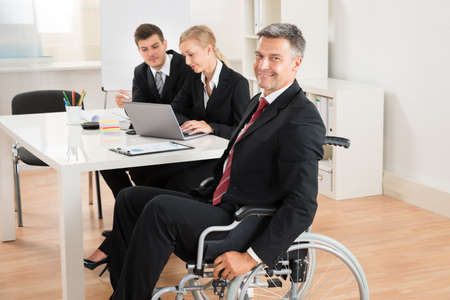 disable: Happy Mature Businessman On Wheelchair With Colleagues In Office