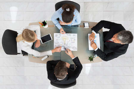 High Angle View Of Businesspeople Discussing Start-up Plan At Desk Stock Photo