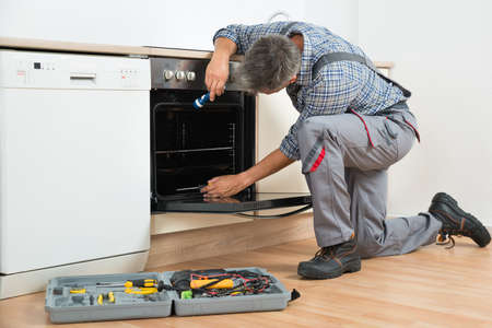 Full length of repairman examining oven with flashlight in kitchen Standard-Bild