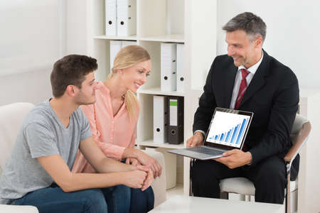 financial consultants: Financial Consultant Showing Graph On Laptop To Happy Young Couple