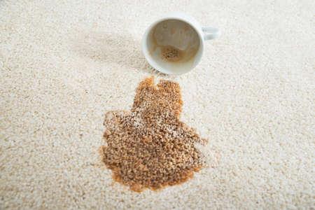 カーペットの上にカップからこぼれるコーヒーのクローズ アップ