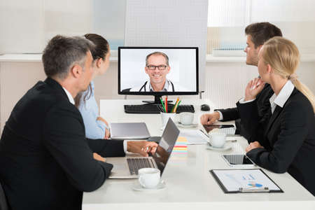 videoconferencing: Team Of Businesspeople Videoconferencing With Doctors On Computer In Office Stock Photo