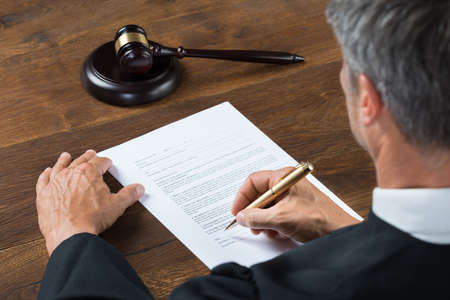 male hand: Rear view of judge writing on paper at table in courtroom Stock Photo