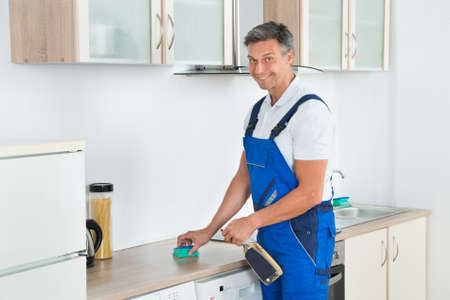 cleaning services: Male janitor cleaning kitchen counter with detergent spray bottle and sponge