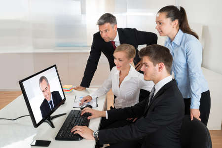 videoconferencing: Businesspeople Videoconferencing With Businessman On Computer In Office
