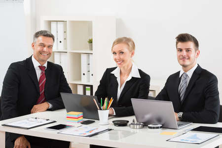 group of business people: Group Of Happy Businesspeople Sitting At Desk