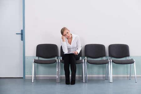 Junge Geschäfts Daydreaming beim Sitzen auf dem Stuhl Standard-Bild
