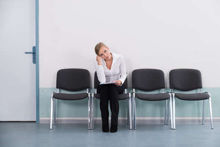 wait: Young Businesswoman Daydreaming While Sitting On Chair Stock Photo