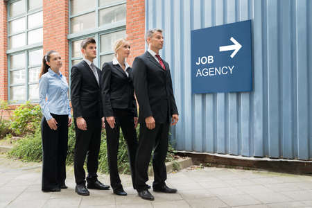 employment: Group Of Businesspeople Waiting In A Row For Interview Near The Job Agency Signboard